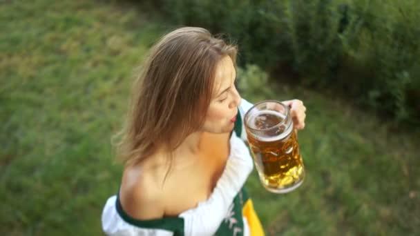 schönes Mädchen auf dem Oktoberfest. Die Frau trägt bayerische Tracht, trinkt Bier und lacht fröhlich. Ansicht von oben