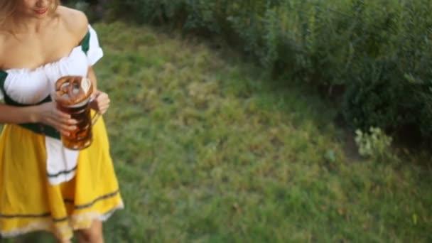 Kellnerin beim Oktoberfest in Deutschland. Ein Mädchen im bayerischen Anzug geht über das Gras und trägt Bier zu den Kunden