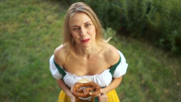 Eine Mädchen in bayrischer Tracht auf dem Oktoberfest Festival teilt ihre Eindrücke, erzählt, beschwert sich. In den Händen einer Frau mit einem großen Glas Bier. Ansicht von oben