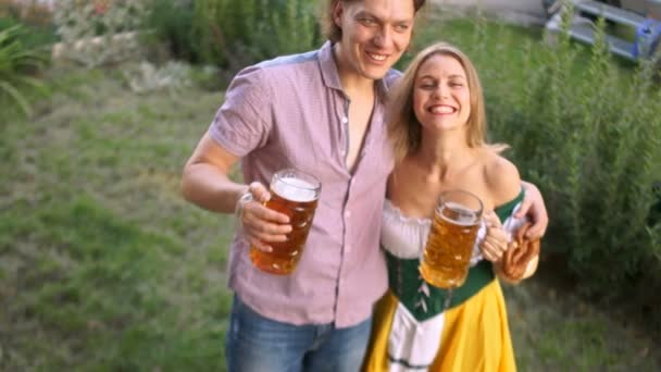 Ein paar junge Leute auf dem Oktoberfest trinken Bier aus großen Gläsern. das Mädchen ist in bayerischer Tracht gekleidet