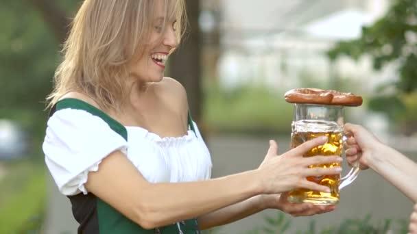 Mädchen in bayerischer Tracht nimmt beim Oktoberfest ein Glas Bier vom Barmann. Die Frau ist glücklich und lacht, sie ist überrascht und fröhlich. unter freiem Himmel