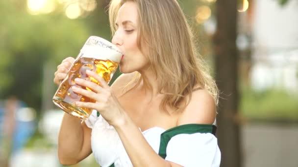 Die reife Frau im traditionellen bayerischen Anzug trinkt Bier und wischt sich peinlich berührt den Schaum auf die Lippen. Rote Lippen, sexy, erotisch. Musikalisches Oktoberfest
