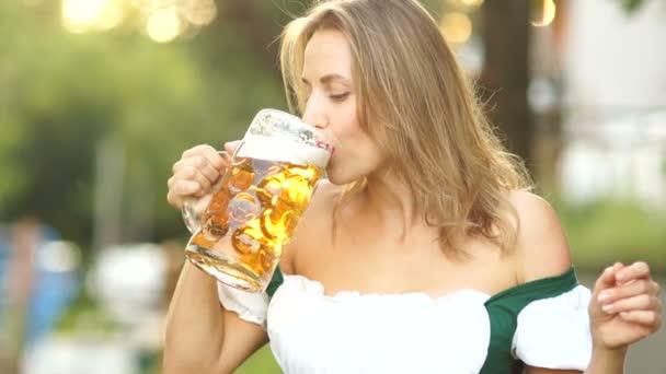 Eine junge Frau im traditionellen bayerischen Anzug trinkt Bier und wischt sich peinlich berührt den Schaum auf die Lippen. Rote Lippen, sexy, erotisch. Musikalisches Oktoberfest.