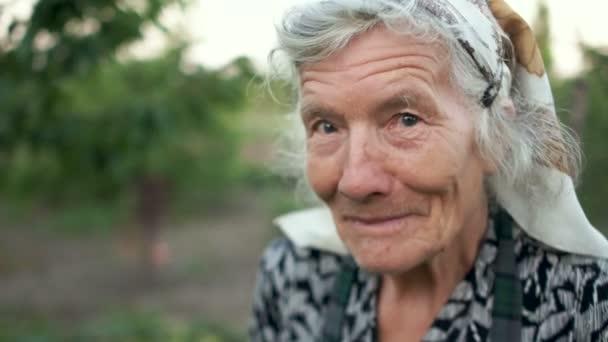 Porträt einer ausdrucksstarken alten Frau im Garten. Der Bauer ist Rentner bei der Arbeit. Landwirtschaft, Leben auf dem Land