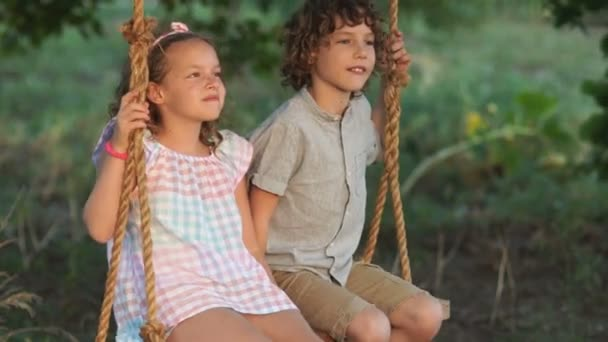 Couple of happy kids hugging and swinging on wooden swing at golden sunset. Brother embracing little sister on a swing. Young love between boy and girl on romantic summer evening