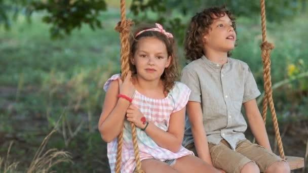 Studenti na dovolené. Chlapec a dívka se houpe na houpačce. Letní romantický západ slunce. Chlapec říká dívka něco