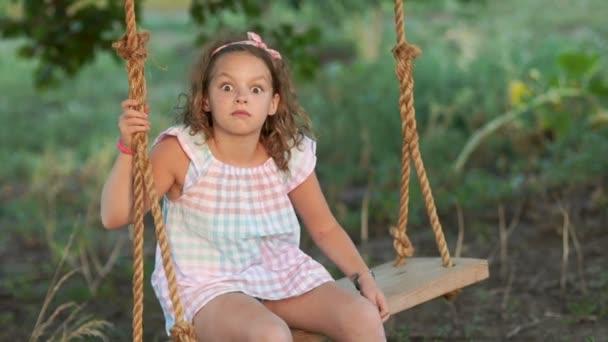 Dívka rohlíky na houpačce a staví tváří, obrátí oči k nosu, zobrazující strabismus