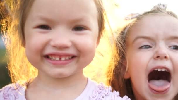 Děti, dvě sestřičky pohrávat, zobrazit jazyk a aby tváře. děti chodí v zahradě, aktivní způsob života, Veselé svátky