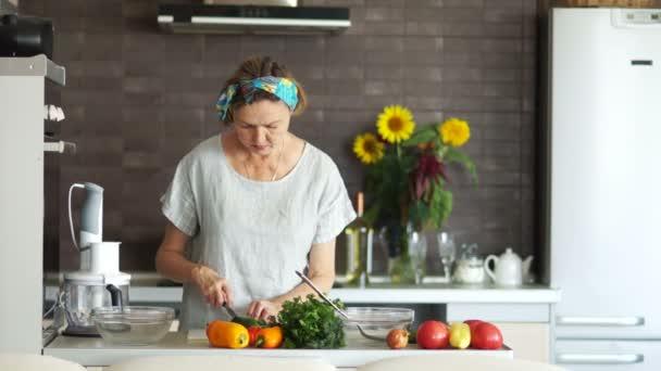 Starší žena vaření potravin v domácí kuchyni. Hospodyně řezy okurky. Moderní, světlé kuchyně interiér, vegetariánství, zdravá výživa