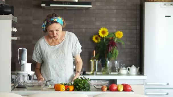 An elderly woman prepares food at home. Modern, bright kitchen interior, vegetarianism, proper nutrition