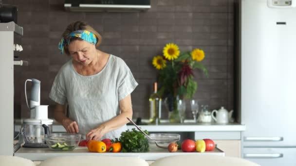 Zralá žena kusy rajčat stojí v kuchyni. Se snaží kus a souhlasně přikývla. Vegetariánská kuchyně, den matek. Žena se připravuje na rodinnou večeři. Den díkůvzdání