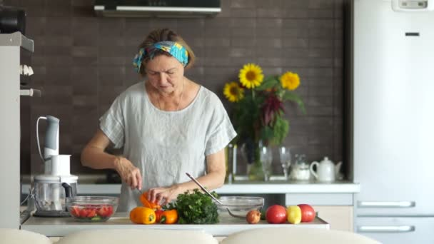 An elderly woman is cutting pepper for a salad. Interior of modern kitchen, healthy lifestyle, mothers day