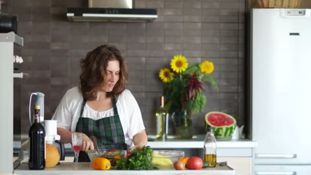 Young attractive housewife prepares a romantic dinner in the kitchen. Bright modern kitchen interior, mothers day