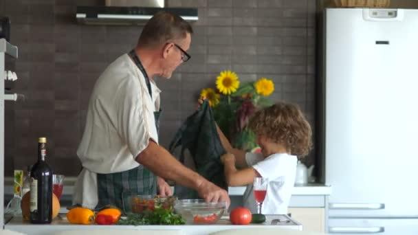 Vnuk pomáhá jeho dědeček uvařit večeři v kuchyni. Zralý muž šaty Kuchyňské zástěry na chlapce. Den otců. Moderní interiér