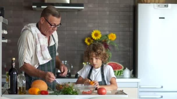 Dědeček a vnuk spolu vařit v kuchyni. Starší muž dává vyzkoušet salát chlapce. Zdravý životní styl, moderní interiér