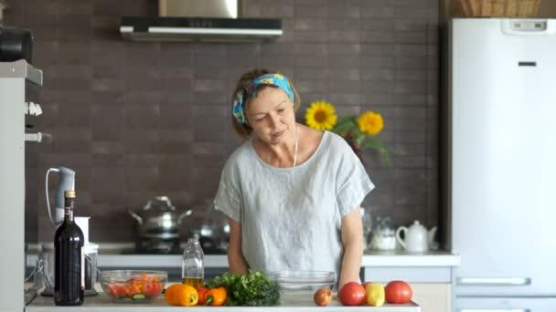 Důchodce tanec v kuchyni. Interiér kuchyně, na stole jsou zelenina. Happy zabezpečené důchod