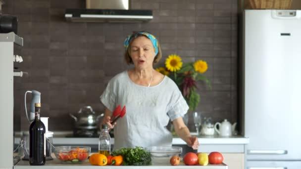 Krásně upravené, krásná žena středního věku důchodce tanec v kuchyni s červeným špachtle pro smažení. Interiér kuchyně, na stole jsou zelenina. Happy zabezpečené důchod