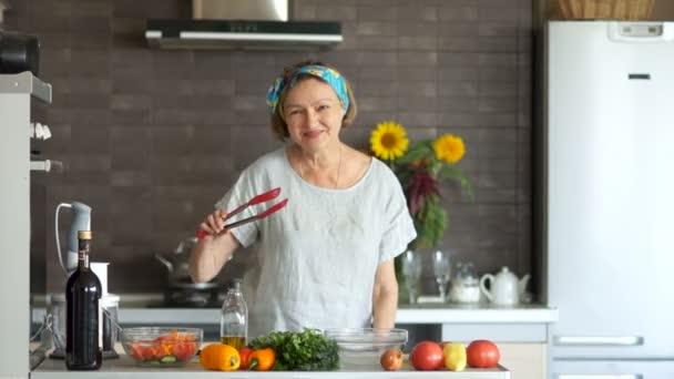 Mature woman dancing with a red spatula for dishes in her kitchen. Modern kitchen interior, bright vegetables on the table, great mood, cooking
