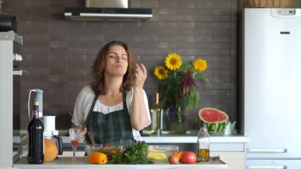 Zdravé jídlo. Mladá sexy žena tancuje v kuchyni, s nožem a chutná salát. Připraví salát, skvělou náladu. Den matek