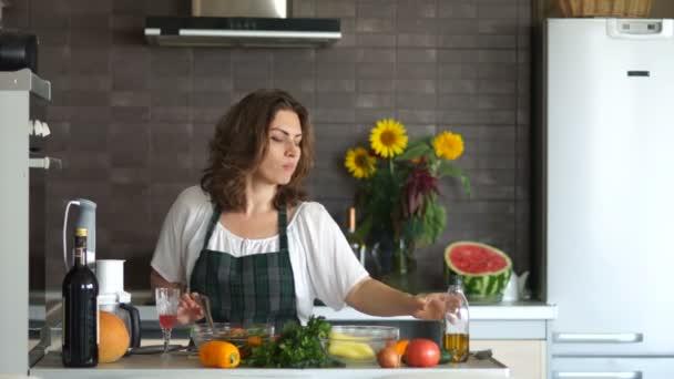Atraktivní kudrnaté mladá žena v kuchyni. Salát salát s olivovým olejem. Zdravá výživa, vegetariánství