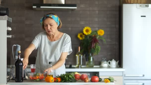 Elderly pensioner in the kitchen prepares a salad and fills it with vegetable oil. Healthy food, vegetarianism as a way of life