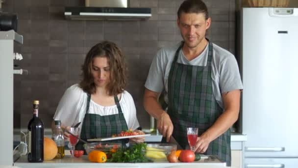 Male and female Cook, couple, husband and wife cook in the kitchen and cut and slice salad and vegetables with a knife