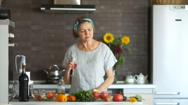 Moderní interiér, Hospodyňka portrét. Starší blondýna žena štěstí v kuchyni drží brýle, červené víno