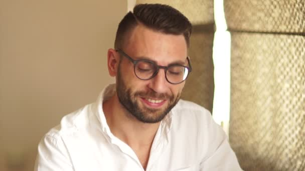 Active businessman in white shirt and glasses smiles broadly while looking into the camera. Close portrait