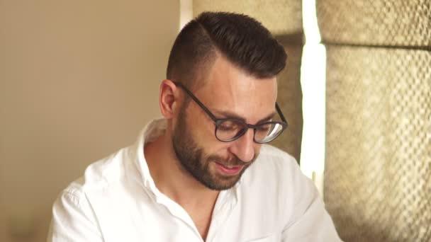 Zavřete portrét atraktivní podnikatel v brýlích a bílou košili. Muž se ohlíží přes své brýle a úsměvy vlídně