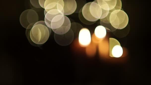 Nahaufnahme von drei brennenden Kerzen mit Weihnachten Licht Hintergrundunschärfe. Dynamik-Fokus, Feier von Weihnachten, Allerheiligen, Halloween