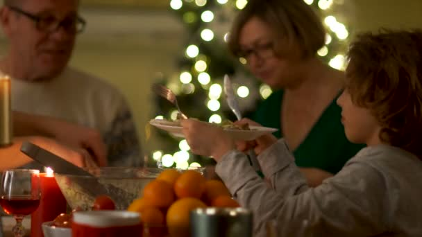 Curly boy at the Christmas table with his grandparents on the background of a New Year tree. The boy holds out his plate for a new portion of food