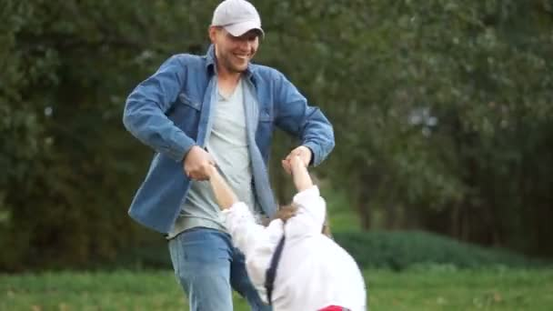 A young man in a cap and denim shirt is spinning a boy, holding his hands. Rest in the park, family holidays