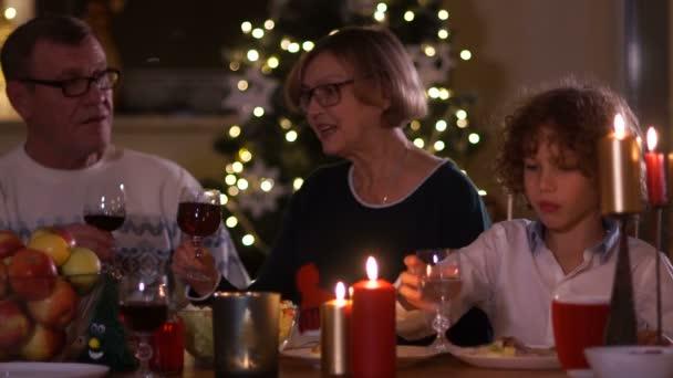 Großvater und Großmutter trinken Rotwein, während sie am Festtagstisch sitzen. Weihnachtstoast, Weihnachtswünsche, glückliche Familie