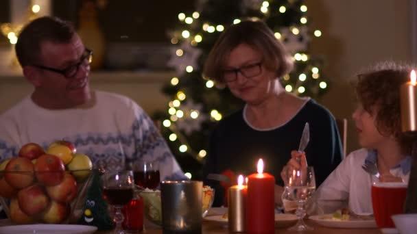 Große Familie mit Kindern zu Hause Weihnachten zu feiern. Festliches Abendessen am Kamin und Weihnachtsbaum. Eltern und Kinder Essen am Feuer Platz in eingerichteten Zimmer. Kind-Beleuchtung Advent Kranz Kerze