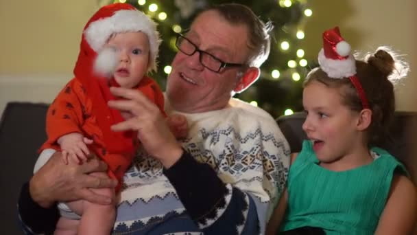 Großvater und zwei Enkelkinder, ein Kleinkind und eine Schülerin auf dem Hintergrund des Weihnachtsbaums. Weihnachtsferien, glückliche Familie
