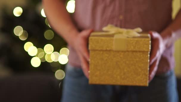 Pánská rukama roztáhnout zlatý box s dárkem, svázané stuhou. Detail vánoční dárek