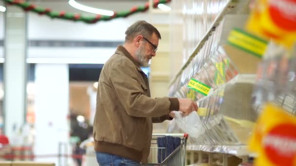 An elderly man buys cereals in the grocery department of a supermarket. The pensioner rolls the cart and puts there products