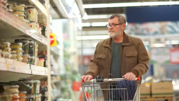 Zralý muž koupí konzervy květák v supermarketu. Zdravé jídlo, hotové saláty, gastronomie v supermarketech