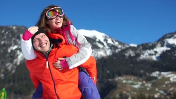 schöne Familienruhe im Skigebiet vor dem Hintergrund der alpinen Berge. Mann und Frau in Skianzügen lachen und winken.