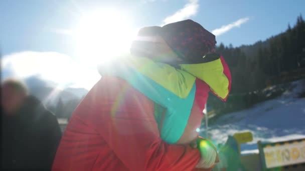 junges glückliches Paar in verschneiten Bergen. der Kerl und das Mädchen umarmen sich vor der untergehenden Sonne. Wintersporturlaub
