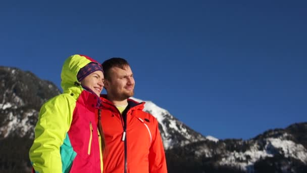 Mature happy couple in snowy mountains. Winter sport vacation. Man and woman wear red ski jackets, family fun