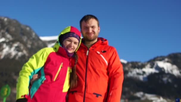 A man and a woman rest in the mountains in winter. Portrait of a loving couple in red ski jackets against the snowy Alpine mountains. Family sports vacation