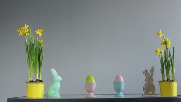 Easter concept. Daffodils in yellow pots, Easter eggs and rabbit figurines. Creative decor, happy easter.