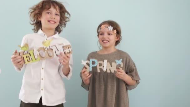 Teenager-Geschwister tanzen mit Frühlingszeichen in der Hand. Osterdekor, Frühlingslandschaft, frohe Ostern