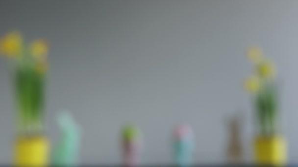 Kreatív húsvéti dekoráció, húsvéti ünnepeket. Húsvéti koncepció. Nárcisz sárga edények, a húsvéti tojás és a nyúl figurák