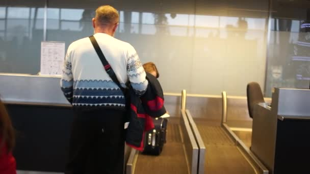Airline Passenger in an Airport. Rear view of a man checking in for a flight at an airport, checking in his baggage