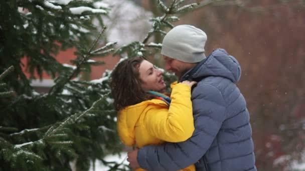 Fiatal pár szerelmes találkoztak a parkban. Gyengéd csók és ölelés, télen időpontja a hó alatt