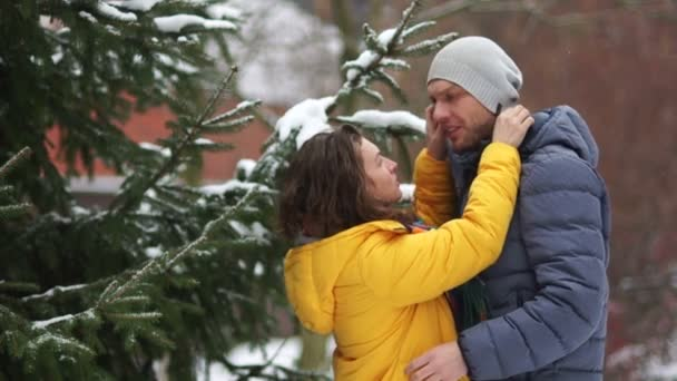 Husband and wife stand embracing in the park near the tree. Winter snowfall, she straightens his hat, he turns away, the couple laughs. Slow Motion