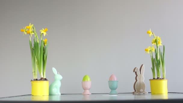 Húsvéti dekoráció az asztalon. Gyermek kezét elrabolják díszített tojás. Cserepes nárcisz, nyúl figura