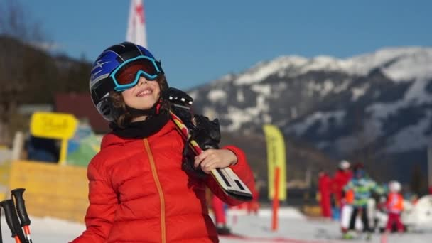 Boy at a ski resort. A child in full equipment for skiing, in a red jacket, glasses and a helmet looks at the sky. The sun shines brightly